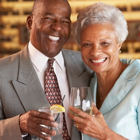 A smiling elderly couple shows how dental implants can restore your smile