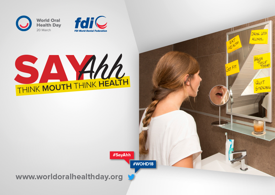 "Woman looking in the mirror saying ""ahh"" for World Oral Health Day 2018"