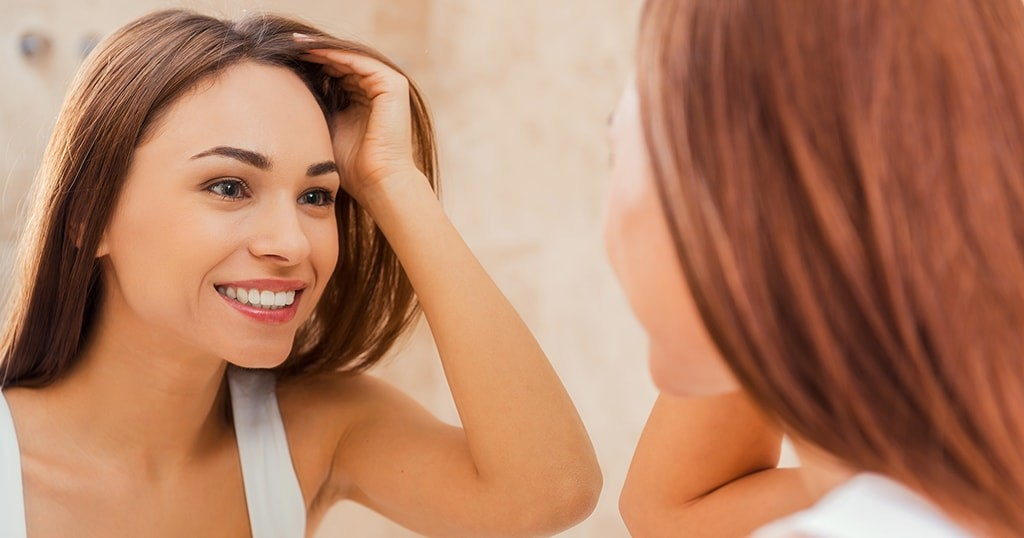 Woman looking at her dental bonding in the mirror