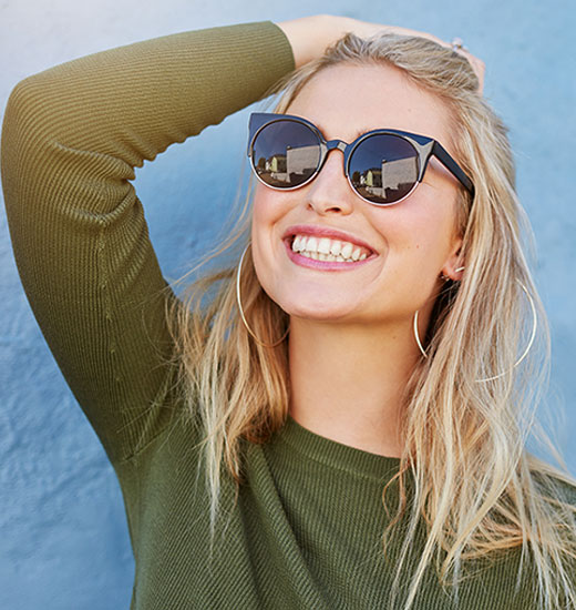 A young blonde woman wearing sunglasses and smiling brightly because of cosmetic dentistry in Tukwila, WA