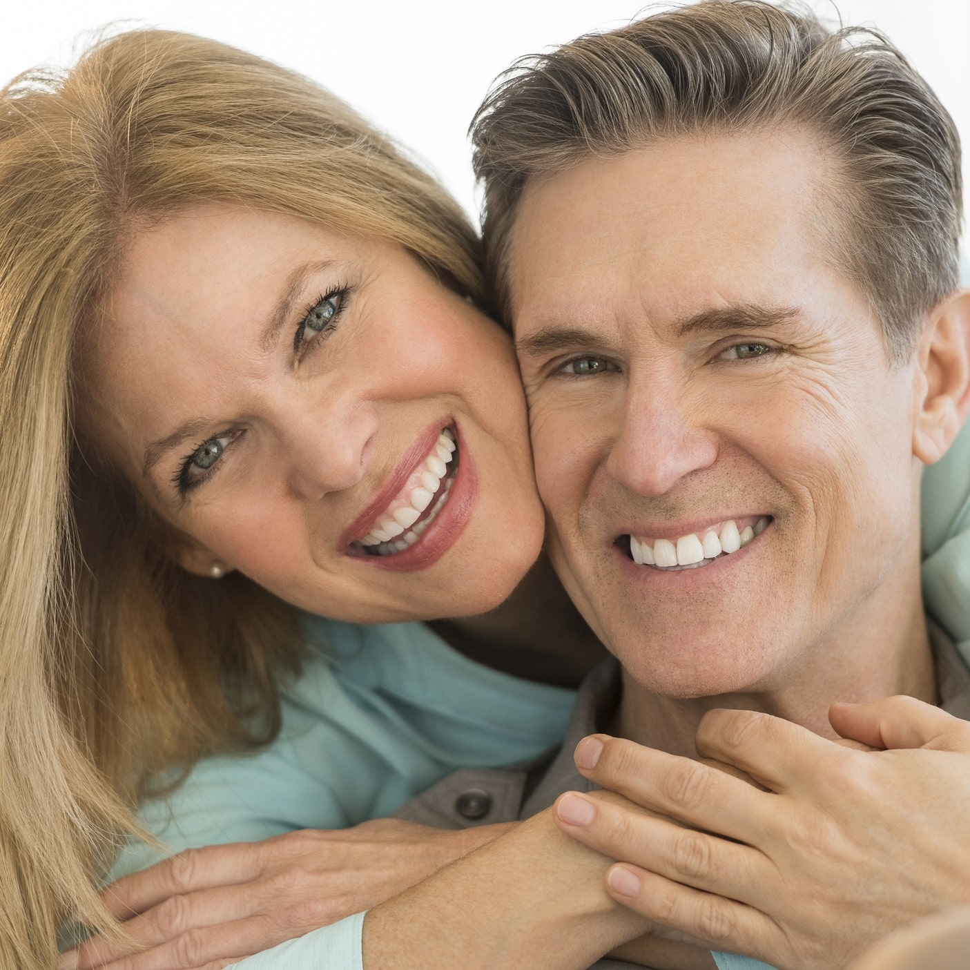 A man and woman smile to show how restorative dentistry has restored the health and beauty of their smiles.