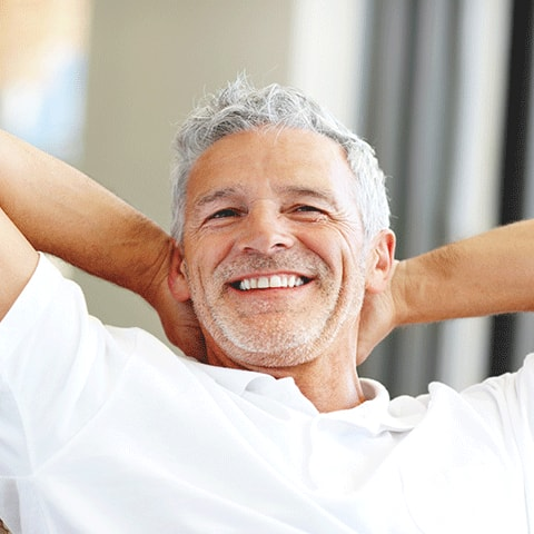 An older man relaxes in a chair with his hands behind his head smiling to illustrate how restorative dentistry can give you back your smile.